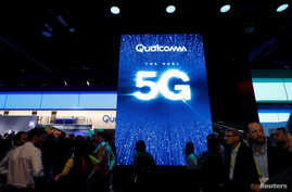 FILE - People walk by a video display promoting 5G connectivity at the Qualcomm booth during the 2019 CES in Las Vegas, Nevada, U.S. Jan. 8, 2019.