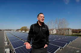 Todd Miller stands next to solar panels on the roof of his solar installation business in Ankeny, Iowa, April 15, 2019.