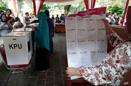 A woman shows a mock national legislature ballot during a polling simulation exercise held by the election commission in Jakarta, Indonesia, Apr. 10, 2019.