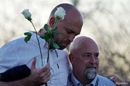 Will Beck, a survivor of the attack at Columbine high school, hugs Lee Andres (R) at the Columbine memorial a day before the school shooting's 20th anniversary, in Littleton, Colorado, April 19, 2019.