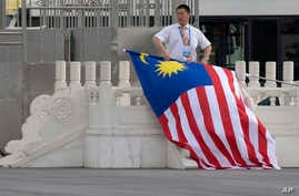 FILE - A worker rolls up a Malaysian national flag after the arrival of Malaysian Prime Minister Najib Razak at Beijing's International Airport ahead of the Belt and Road Forum in Beijing, China, May 12, 2017.