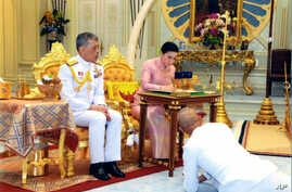 In this photo released by Bureau of the Royal Household ,Thailand's King Maha Vajiralongkorn Bodindradebayavarangkun, left, sits with Queen Suthida Vajiralongkorn Na Ayudhya as they sign their marriage certificates at Ampornsan Throne Hall in Bangkok...
