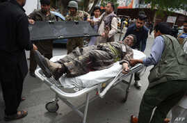 A wounded Afghan man is brought on a stretcher to an Italian aid organization's hospital, as Afghan security forces battled an ongoing attack by Taliban militants on a compound housing an international aid organisation in Kabul on May 8, 2019.