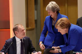Britain's Prime Minister Theresa May and Germany's Chancellor Angela Merkel look at a tablet next to European Council President Donald Tusk, ahead of an extraordinary European Union leaders summit on Brexit at EU Council headquarters in Brussels, Be...