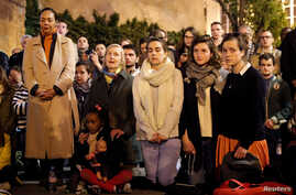 People pray and sing religious songs next to Notre Dame Cathedral after a fire broke out, in Paris, April 15, 2019.