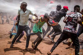 Supporters of Ugandan musician turned politician Robert Kyagulanyi, commonly known as Bobi Wine, run away from a water cannon as they gather at Busabala, where he was planning to hold a news conference, April 22, 2019.