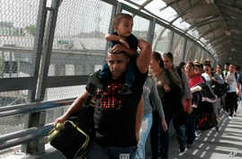 In this April 29, 2019, photo, Cuban migrants are escorted by Mexican immigration officials in Ciudad Juarez, Mexico, as they cross the Paso del Norte International bridge to be processed as asylum seekers on the U.S. side of the border. Burgeoning numbers of Cubans are trying to get into the U.S. by way of the Mexican border, creating a big backlog of people waiting on the Mexican side for months for their chance to apply for asylum. (AP Photo/Christian Torres)