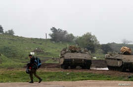 FILE - An Israeli soldier walks past armored Israeli military vehicles in the Israeli-occupied Golan Heights, March 25, 2019.