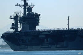 FILE - The aircraft carrier USS Theodore Roosevelt, with sailors manning the rails, leaves port on deployment, Oct. 6, 2017.