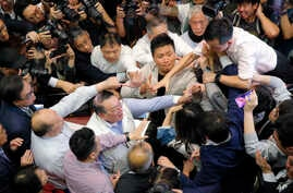 Pro-democracy and pro-Beijing lawmakers scuffle in the chamber of the Legislative Council in Hong Kong, May 11, 2019.
