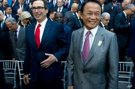 FILE - U.S. Treasury Secretary Steve Mnuchin, left, and Japan's Finance Minister Taro Aso attend the International Monetary Fund (IMF) Governors group photo at World Bank/IMF Spring Meetings, in Washington, April 21, 2018.
