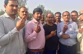 Voters emerge from a polling station in Western Uttar Pradesh holding up their fingers which get marked with ink after they cast ballots.