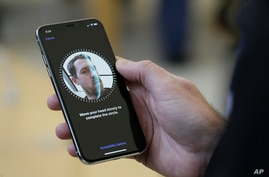 An Apple employee demonstrates the facial recognition feature of the new iPhone X at the Apple Union Square store in San Francisco.