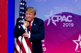 President Donald Trump hugs the American flag in Oxon Hill, Md., March 2, 2019.