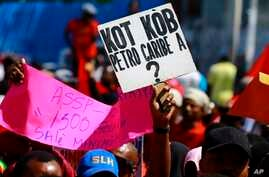 "A protester holds up a sign that asks in Creole: ""Where is the Petro-Caribe money?"" during a demonstration in Port-au-Prince, Haiti"
