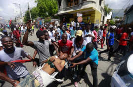 Anti-government protesters carry the body of man toward the vehicle of police, who they blame for his death, during a demonstration in Port-au-Prince, Haiti, Sunday, June 9, 2019.