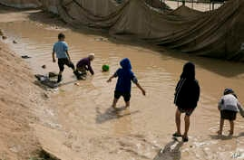 FILE - children play in a mud puddle in the section for foreign families at Al-Hol camp in Hasakeh province, Syria.