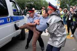 Kazakh police detain a demonstrator in Almaty, Kazakhstan, June 12, 2019, during protests against presidential elections.