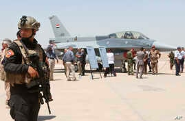 FILE - A member of the Iraqi SWAT team stands guard as security forces and others gather next to a U.S.- made F-16 fighter jet during the delivery ceremony at Balad air base, Iraq, July 20, 2015.