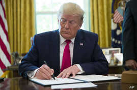 President Donald Trump listens to a reporter's question after signing an executive order to increase sanctions on Iran.