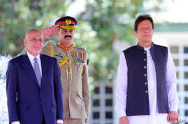 Visiting Afghan President Ashraf Ghani, left, reviews guard of honor with Prime Minister of Pakistan Imran Khan in Islamabad, Pakistan, June 27, 2019, in this photo released by the Press Information Department.