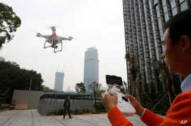 FILE - A staff member from DJI Technology Co. demonstrates a drone in Shenzhen, south China's Guangdong province, Dec. 15, 2014.