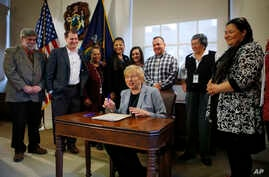 Maine Gov. Janet Mills signs a bill to establish Indigenous Peoples' Day, at the State House in Augusta, Maine, April 26, 2019.