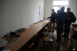 FILE - Belsat journalists examine empty tables after Belarusian police conducted a search and confiscated equipment in the broadcaster's office in capital Minsk, Belarus, March 31, 2017.