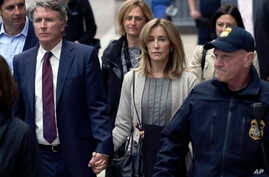 Felicity Huffman, center, departs federal court with her brother Moore Huffman Jr., left, May 13, 2019, in Boston, where she pleaded guilty to charges in a nationwide college admissions bribery scandal.
