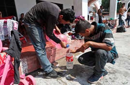 Central American migrants traveling in a caravan to the U.S. collect water as they rest at the San Francisco Catholic church in Tonala, Chiapas State, Mexico,  April 23, 2019.