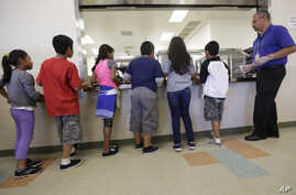 FILE - Detained immigrant children line up in the cafeteria at the Karnes County Residential Center, a detention center for immigrant families, in Karnes City, Texas, Sept. 10, 2014.