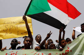Protesters wave Sudanese flags, hold banners and chant slogans during a demonstration in front of the Defense Ministry in Khartoum, Sudan, April 18, 2019.