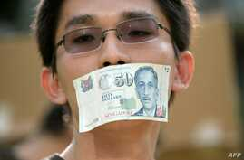 FILE - A protester covers his mouth with a Singapore fifty-dollar note during a rally at a free-speech park called Speakers' Corner in Singapore, June 8, 2013.