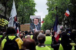 """Yellow vest protesters, one carrying a placard with a picture and a quote of French President Emmanuel Macron (""""Let them come get me""""), march in Paris, May 4, 2019."""