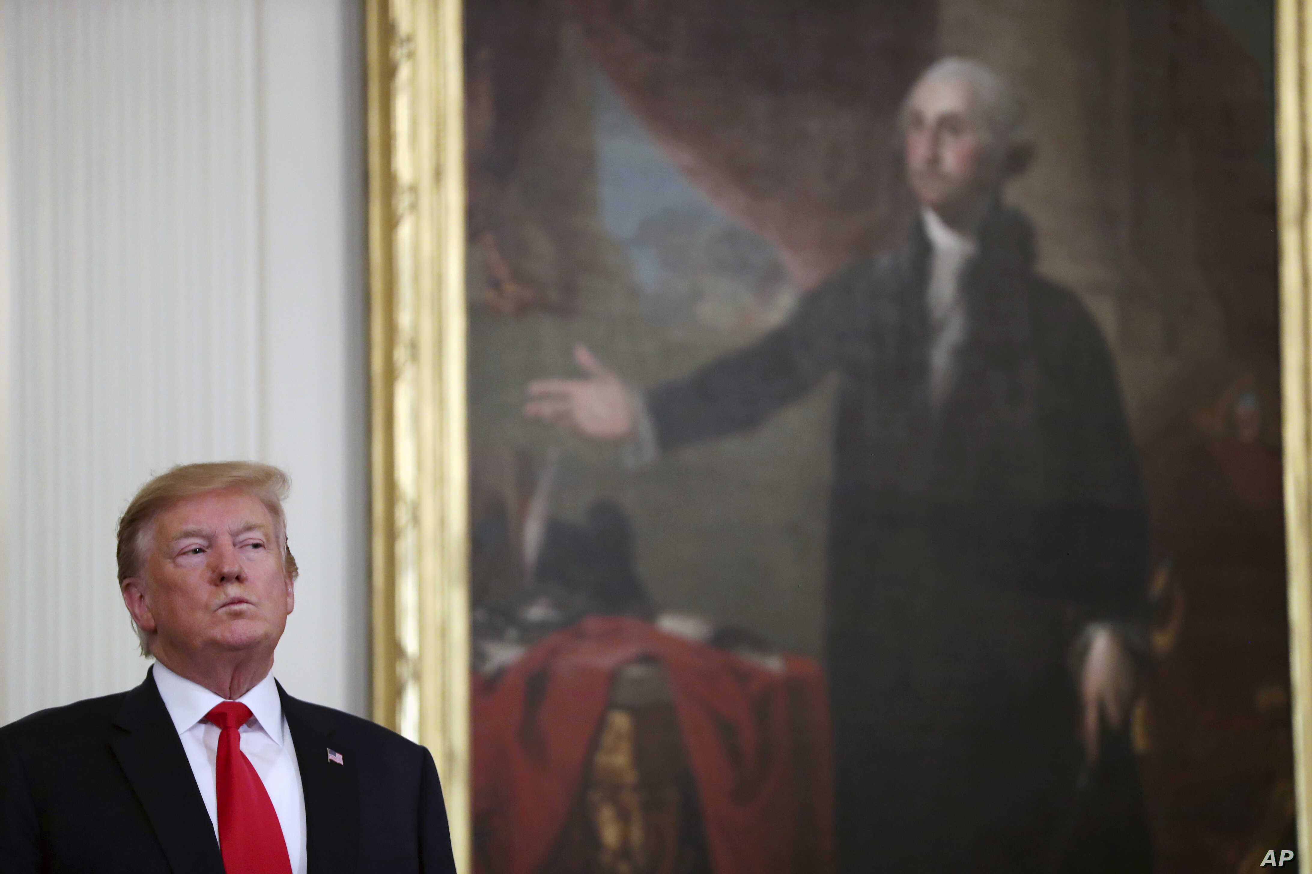 FILE - President Donald Trump stands near a portrait of George Washington in the East Room of the White House, April 18, 2019, in Washington.