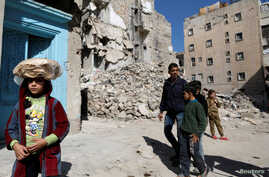 A girl carries a stack of bread on her head as she walks near rubble of damaged buildings in Aleppo's Kalasa district, Syria, April 12, 2019.
