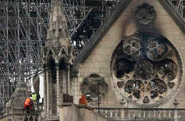 Experts inspect the damaged Notre Dame cathedral after the fire in Paris, April 16, 2019, assessing the blackened shell of Paris' iconic cathedral to establish next steps to save what remains after a devastating fire destroyed much of the almost 900-...