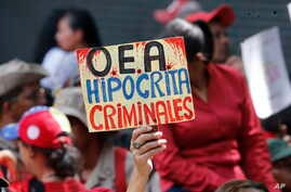 """A supporter of Venezuela's president Nicolas Maduro, holds a sign that reads in Spanish """"OAS Hypocrites, Criminals"""" during a government rally in Caracas, Venezuela,, April 27, 2019."""