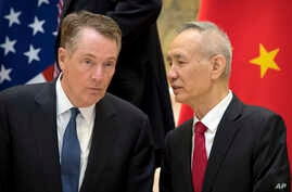 FILE - Chinese Vice Premier Liu He (R) talks with U.S. Trade Representative Robert Lighthizer, while they line up for a group photo at the Diaoyutai State Guesthouse in Beijing,Feb. 15, 2019.