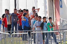"FILE - Children line up to enter a tent at the Homestead Temporary Shelter for Unaccompanied Children in Homestead, Fla., April 19, 2019. Immigrant advocates say the U.S. government is allowing migrant children to languish in ""prisonlike conditions..."