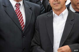 FILE - Then Algerian prime minister Ahmed Ouyahia (L) stands next to Said Bouteflika, brother of the then Algerian president Abdelaziz Bouteflika, in Algiers, May 19, 2012.