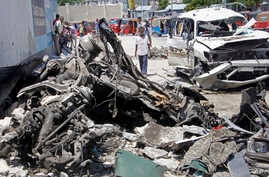 Somalis walk near the wreckage after a suicide car bomb attack in the capital Mogadishu, Somalia, May 22, 2019.