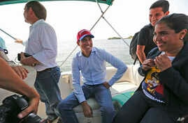 Juan Guaidó, opposition leader and self-proclaimed interim president of Venezuela, sits on a boat with staff members before crossing Maracaibo Lake to reach the town of Cabimas, Venezuela where he will lead a rally, April 14, 2019.