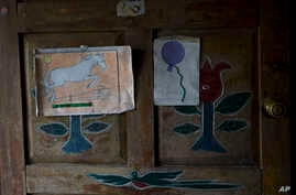 FILE - Artwork by Felipe Gomez Alonzo, an 8-year-old Guatemalan boy who died in U.S. custody, is taped to a door of the Gomez home in Yalambojoch, Guatemala, Dec. 29, 2018. U.S. officials said a Guatemalan teen died April 30, 2019, in a Texas hospita...
