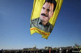 FILE - A banner with a picture of imprisoned Kurdish rebel leader Abdullah Ocalan is seen during a protest in Qamishli, Syria, Jan. 30, 2018.
