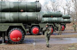 """FILE - Russian servicemen stand next to a new S-400 """"Triumph"""" surface-to-air missile system after its deployment at a military base outside the town of Gvardeysk near Kaliningrad, Russia, March 11, 2019."""