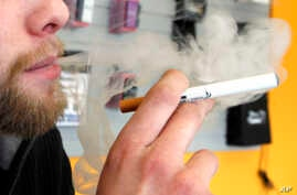 FILE - A sales associate demonstrates the use of an electronic cigarette and the smoke-like vapor that comes from it, in Aurora, Colorado, March 2, 2011.