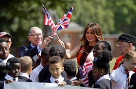 FILE - U.S. first lady Melania Trump and Philip May, the husband of British Prime Minister Theresa May, wave their respective national flags during a visit to British military veterans at The Royal Hospital Chelsea in central London, July 13, 2018.
