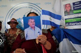FILE - A woman holds a picture during a news conference at the Permanent Commission of Human Rights of Nicaragua (CPDH) headquarters to demand the release of the demonstrators detained during last year's protests against Nicaraguan President Daniel O...