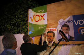 Members of Spain's far-right party VOX put up a campaign poster, while main candidates for Spanish general elections debate during a live televised debate ahead of general elections in Madrid, outside a polling station in Ronda, southern Spain April ...